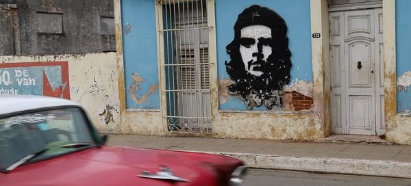 Kubareisen-Santa-Clara-Hauswand-mit-CheGuevara-rotes-Auto