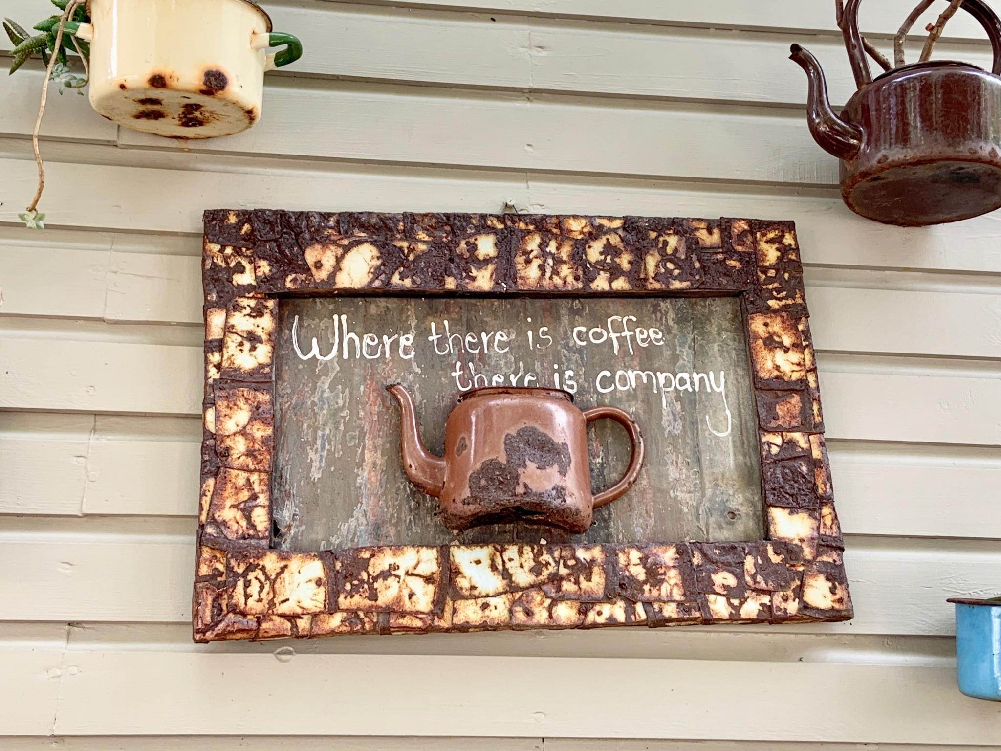 Alte Kaffeekanne hängt als kunstvolles Objekt an Holzwand