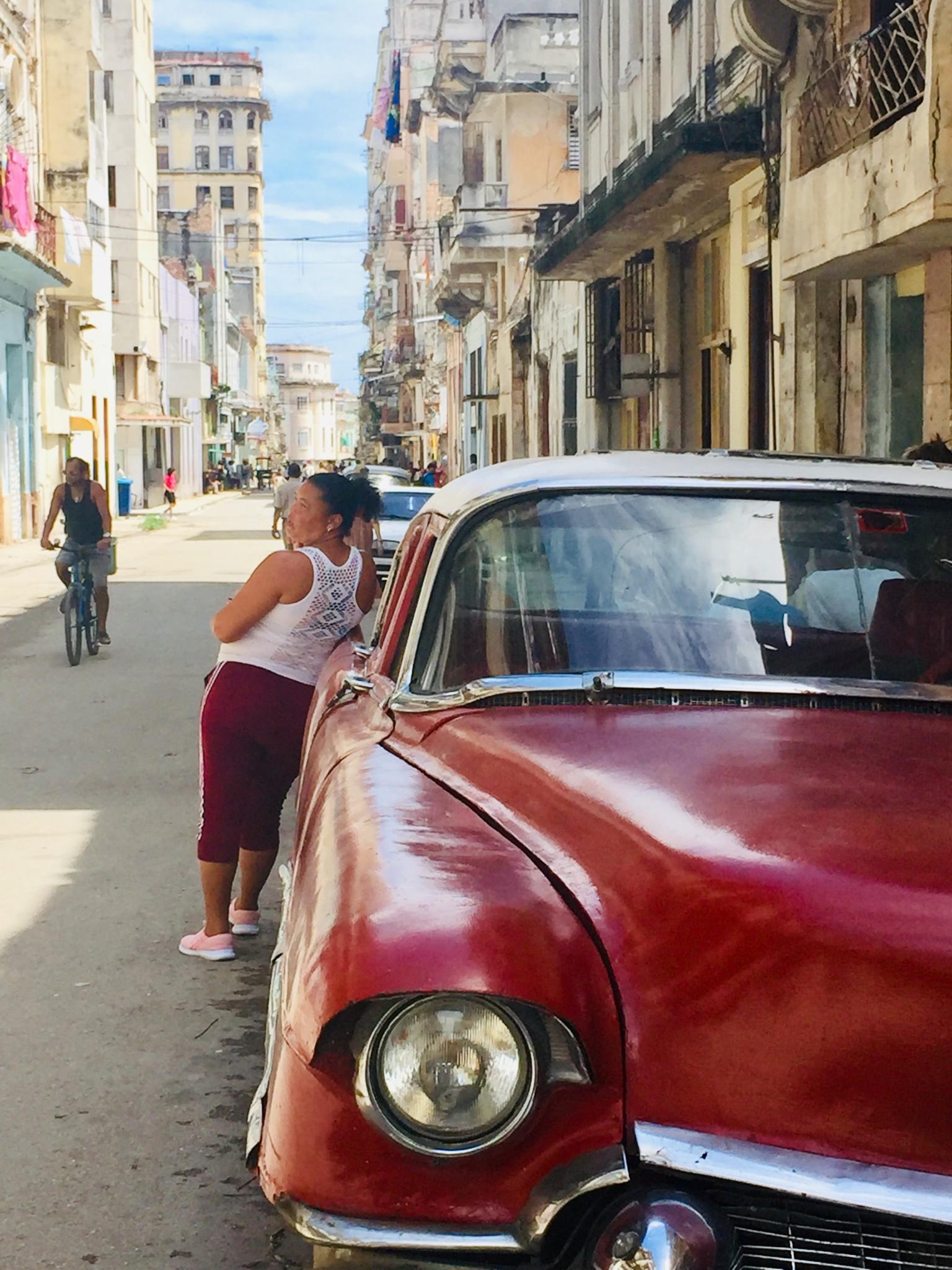 Kuba-Havanna-Centro-Frau lehnt an rotem Oldtimer-IMG_7936-bk